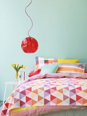 a colorful spring bedroom with blue walls, a bed with colorful bedding, a red pendant lamp and bold blooms in a vase