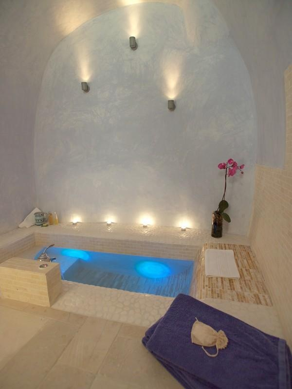 a styled sunken bathtub with a curved for comfortable leaning, lights and potted blooms for an atmosphere