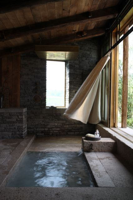 an outdoor-indoor space done in stone and concrete plus a sunken bathtub or plunging pool