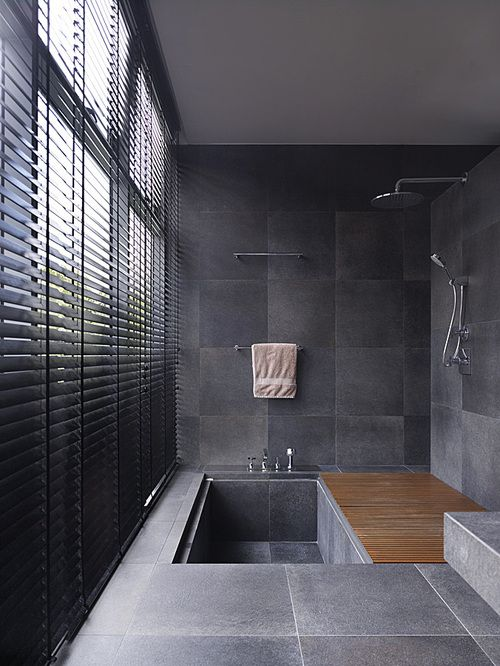 a minimalist tiled bathroom with a tiled sunken bathtub and a wooden mat is amazing for a contemporary space