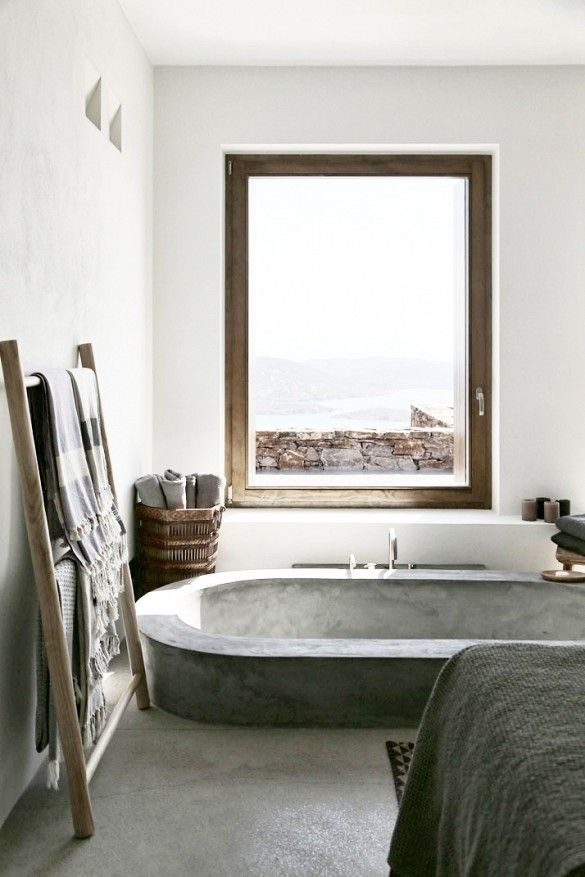 a minimalist bathroom with concrete and stone, with a sunken concrete bathtub, a view to the sea