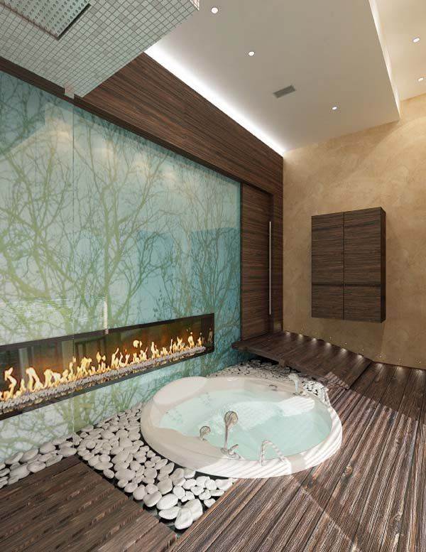 a sunken round bathtub with white pebbles around, with a wooden deck and a built in fireplace for more relaxation