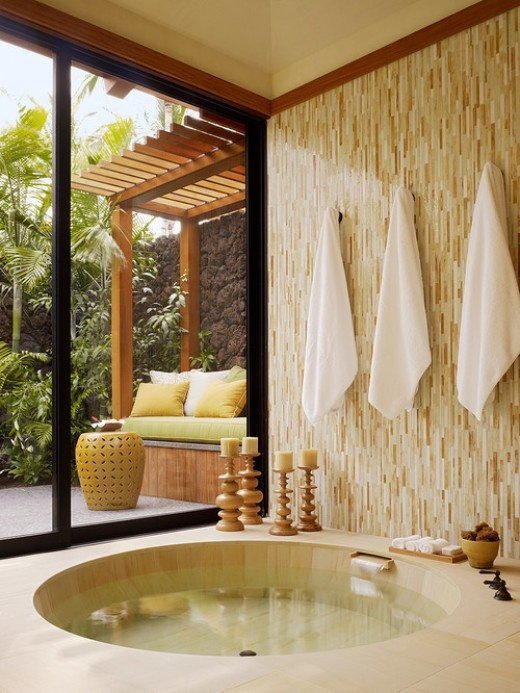 a tropical bathroom done in neutrals, with a round sunken bathtub and sliding doors to the garden for a view and more sunshine