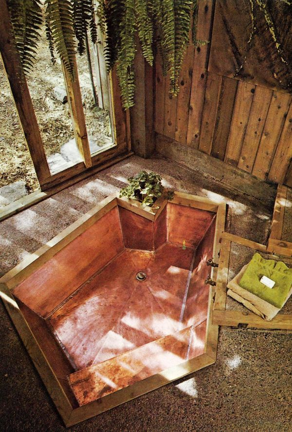 a natural bathroom with a stone floor, pallet wood walls and an asymmetrical bathtub clad with copper inside it