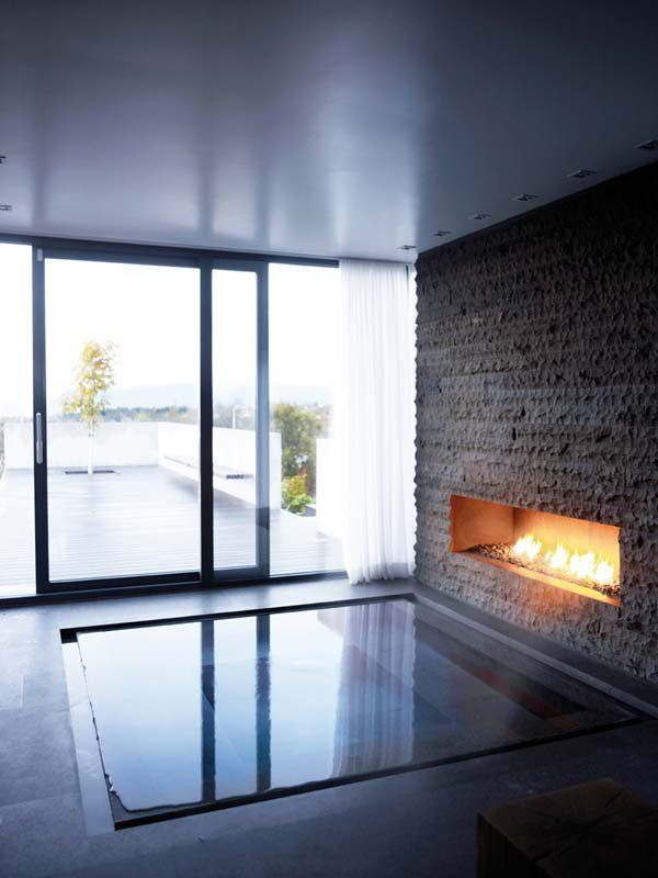 a large sunken bathtub with a faux stone wall and a fireplace in it is a gorgeous relaxing space