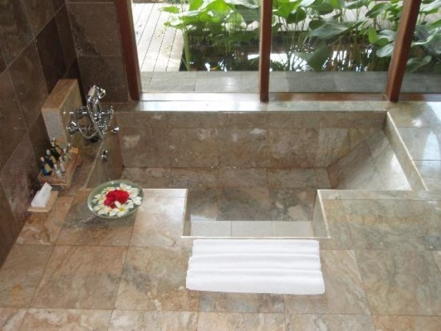 a natural looking bathroom with neutral stone tiles and a sunken bathtub with steps and a glazed wall with a view
