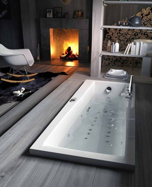 a sunken bathtub with a deck right in the bedroom with a fireplace, looks very natural and very relaxing and enjoyable