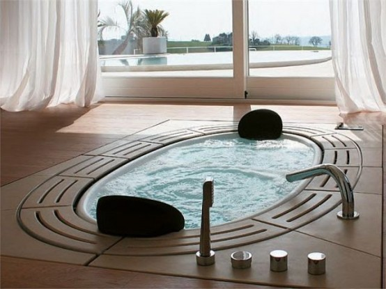 a sunken oval bathtub with tiles around plus an entry to the terrace to fill the space with light and air