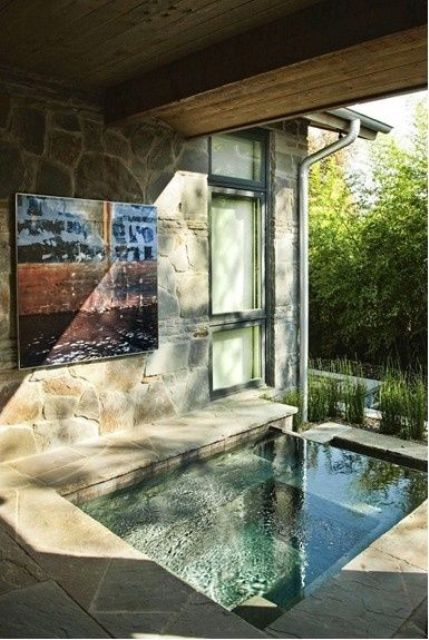 an indoor-outdoor bathroom with a sunken bathtub or pool, done with stone and tiles plus sunshine coming from outside
