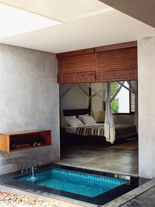 a sunken bathtub with tiles inside and stone around, with shades that separate it from the bedroom