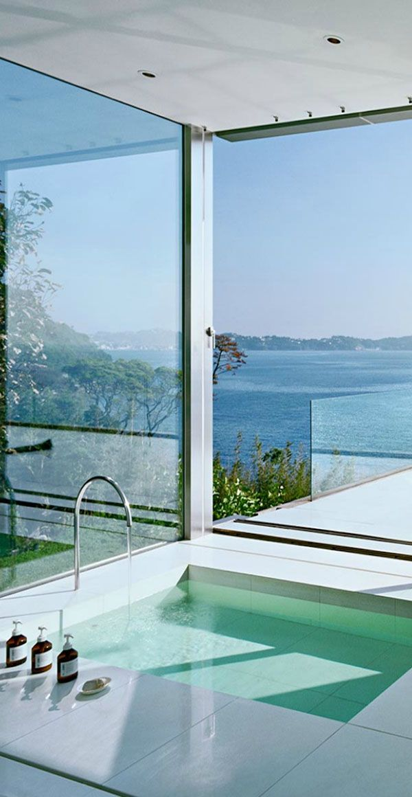 a minimalist bathroom all glazed, with a view, with sunshine and air, with a sunken bathtub that takes maximum of these views