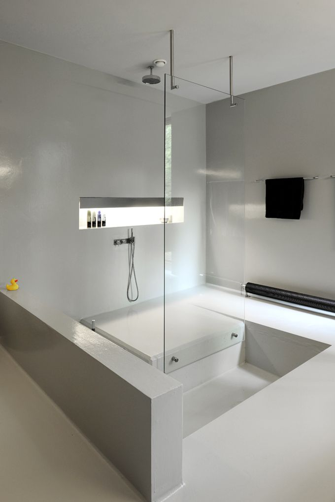 a minimalist white bathroom with a shower space and a sunken bathtub looks all sleek and chic