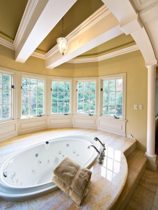 a large and welcoming bathroom with lots of windows and beams on the ceiling, with a large oval tub plus a stone deck around