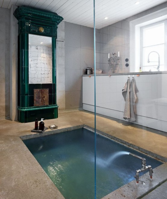 an eclectic bathroom with a green hearth, a sunken bathtub in concrete plus a white console