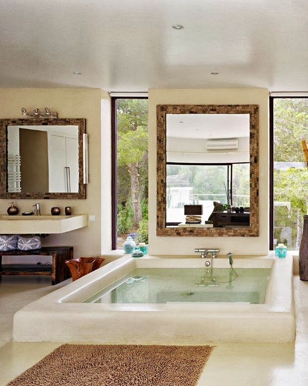 a stylish bathroom with a large sunken bathtub, with vertical windows for views and a large window that keeps your privacy