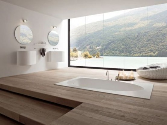 a large minimalist bathroom with a sleek wooden floor and a sunken bathtub plus a fantastic view through a panoramic window