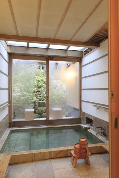 a sunken tiled ofuro-style bathtub with stools and a view of a Japanese garden through the forsted glass sliding doors