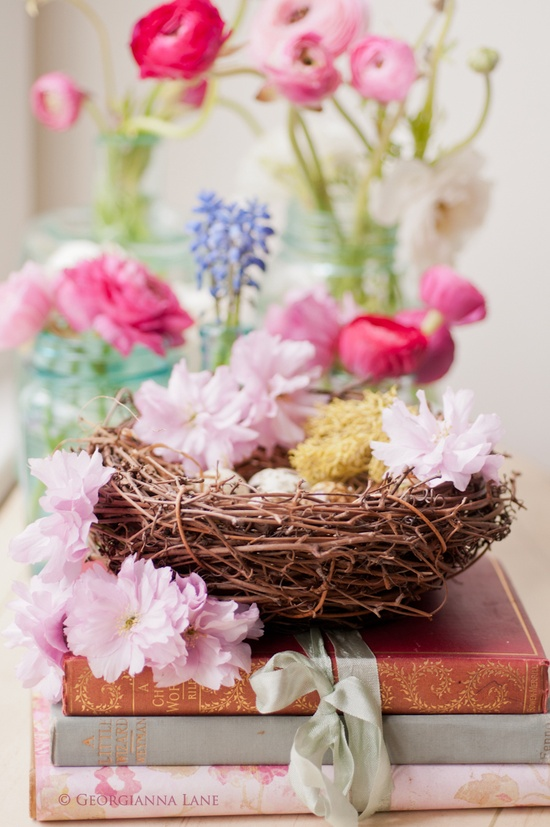 a nest with pink blooms and faux eggs is a cool idea of an Easter centerpiece