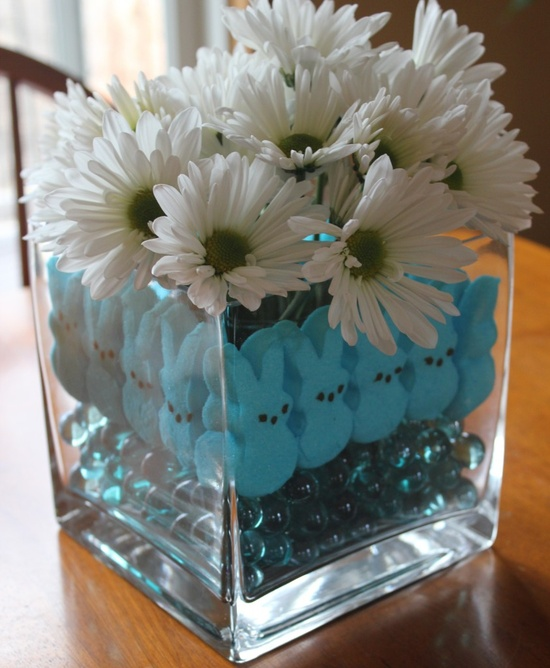 a simple white flower arrangement in a jar with blue beads and blue bunnies for Easter