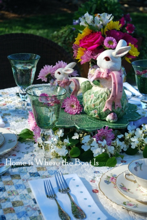 an Easter centerpiece of a leaf-shaped bowl, lots of spring blooms and a flower arrangement on top