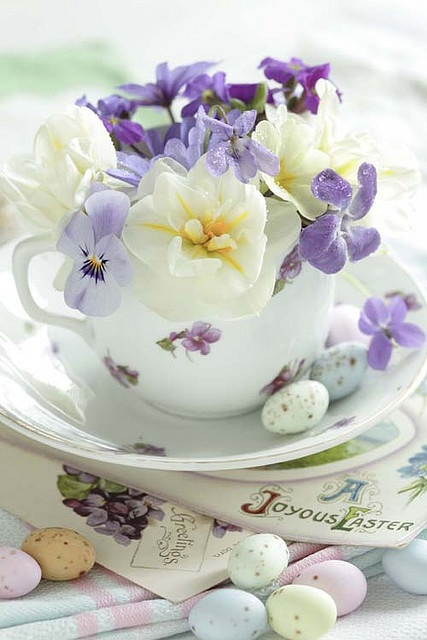 a vintage floral tea pot with some sprign blooms and pastel eggs on the saucer