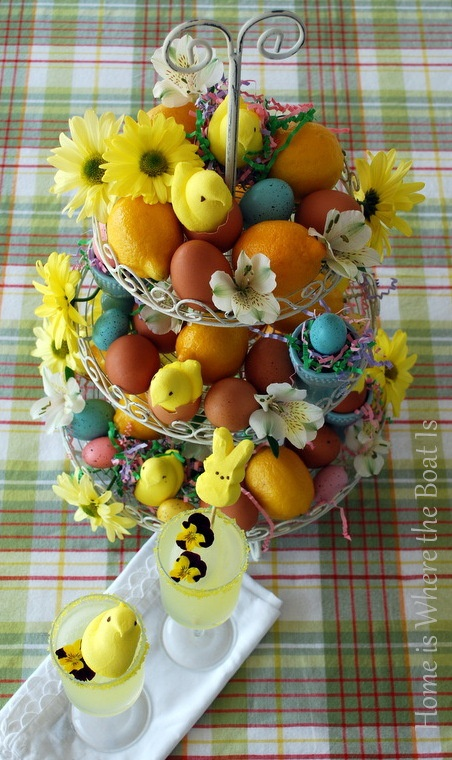 a cupcake stand filled with colorful eggs, blooms and citrus is a bright Easter centerpiece