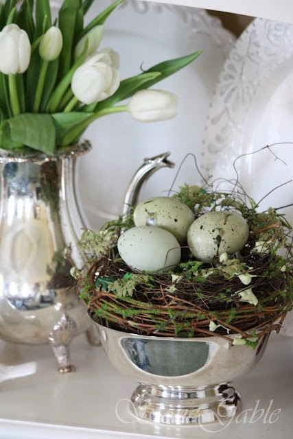 a silver bowl with a nest, moss and speckled eggs and a white tulip flower arrangement