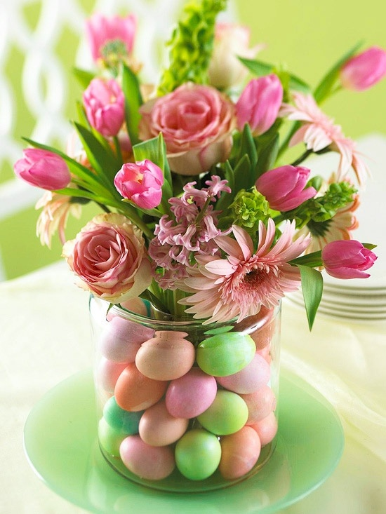 an Easter flower arrangement done in pink and with bright faux eggs in the jar