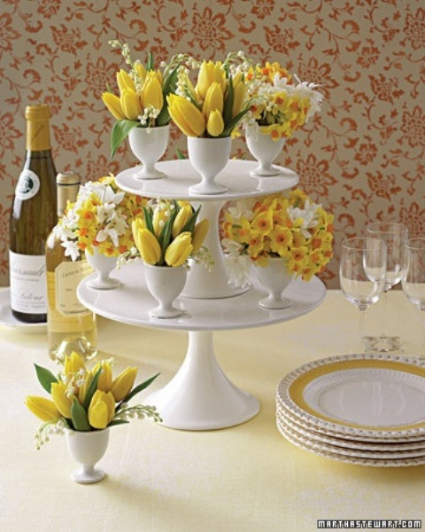 a cupcake stand with egg holders with spring blooms in white and yellow for an Easter centerpiece