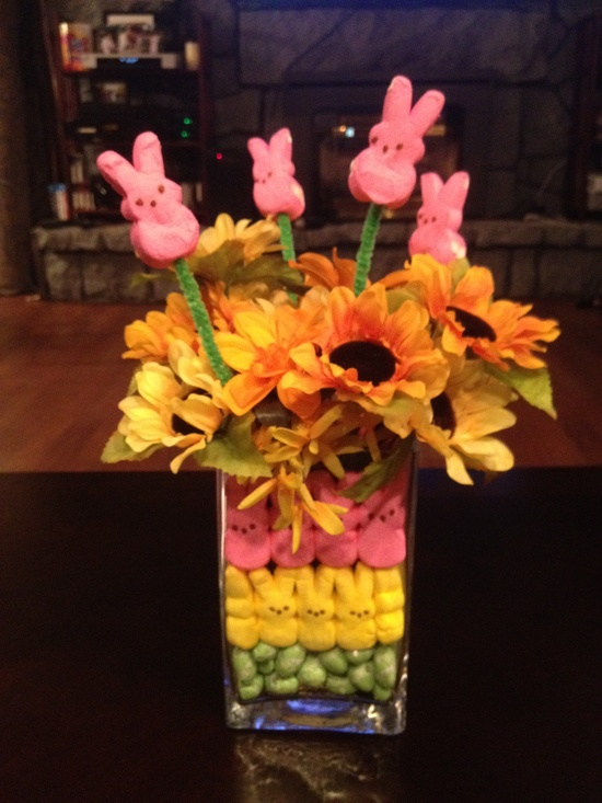 a clear vase filled with colorful bunnies and with bright blooms and bunnies on sticks for Easter