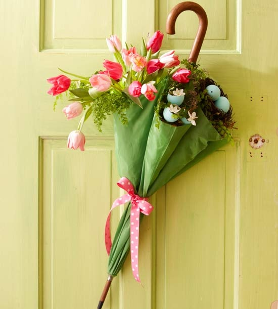 a green umbrella filled with pink tulips and a nest with blue eggs for Easter decor