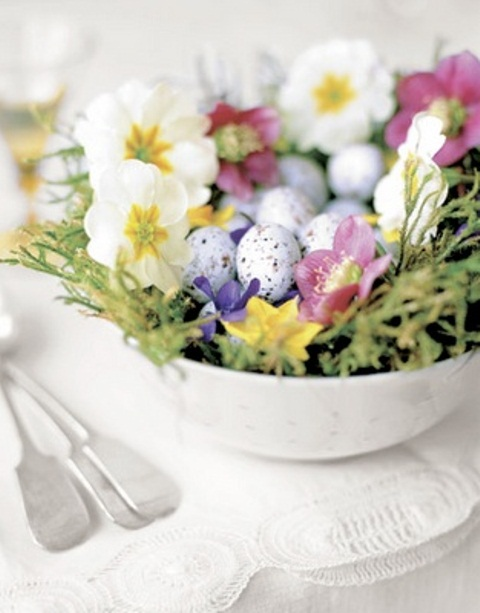 a bowl with grass, spring blooms and pastel speckled fake eggs for Easter