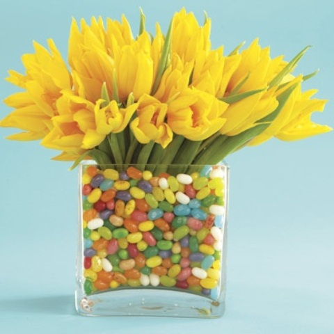 a clear vase with colorful candies and bright yellow tulips for a bold Easter centerpiece