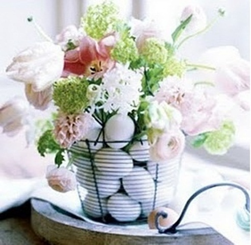 a wire basket with pink, red and white blooms and green hydrangeas for Easter