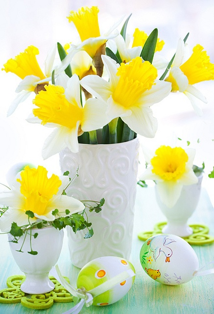 a vase and egg holders with yellow daffodils is a timeless Easter centerpiece idea