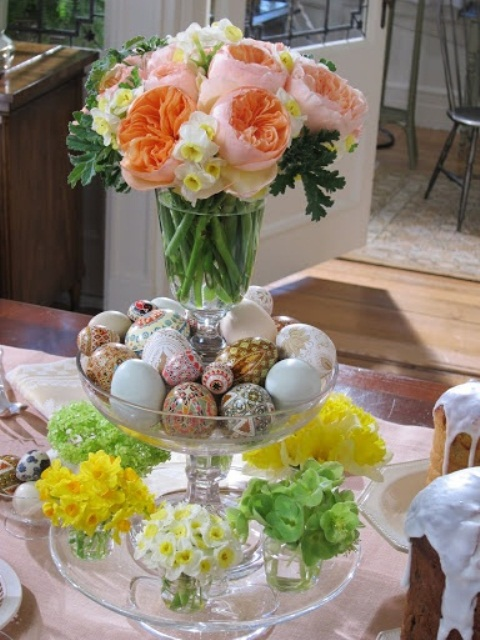a stand of glass bowls with tiny spring flower arrangements, decorated eggs and a pink bloom top