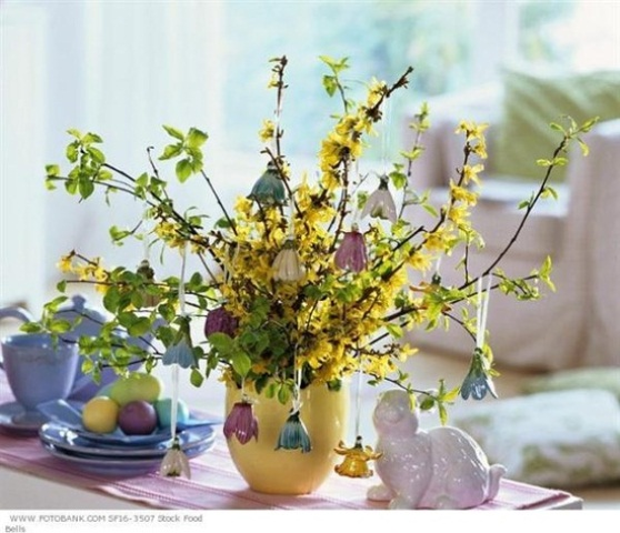 yellow blooming branches and greenery and bells hanging on the branches for a whimsy Easter centerpiece