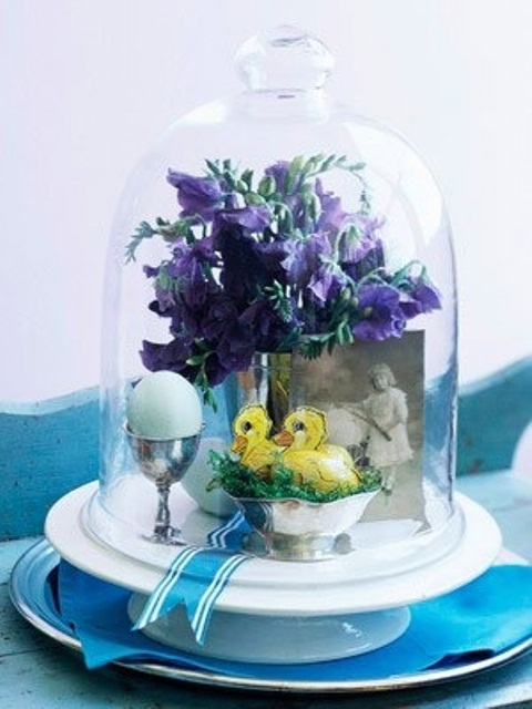 a cute cloche arrangement with a photo, some spring blooms, fake birds and an egg for Easter