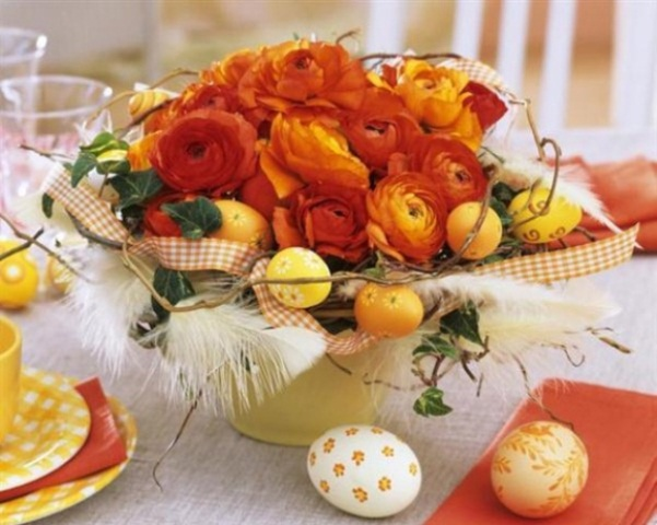 a bright Easter centerpiece with citrus and red and orange flowers, feathers and checked ribbons