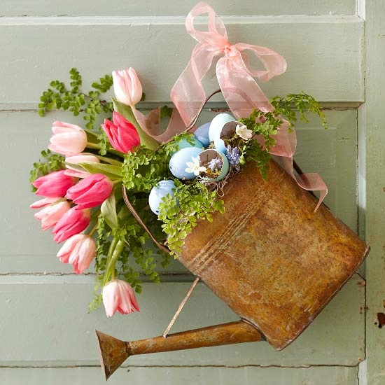 a vintage watering can with greenery, pink tulips and blue eggs for Easter decor