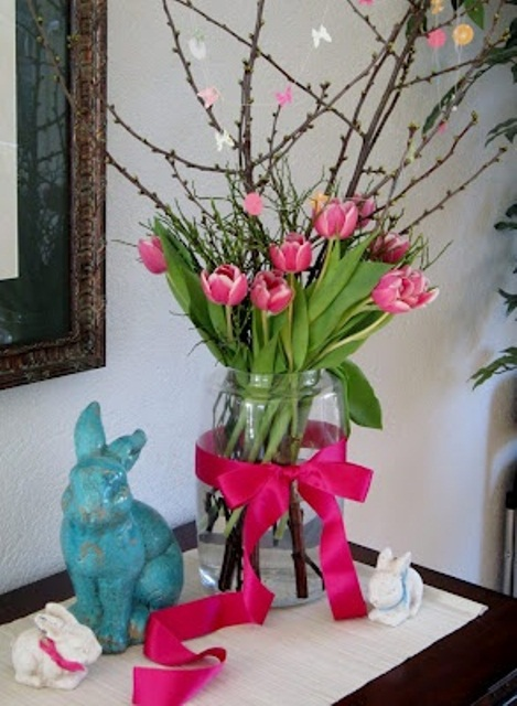 an Easter arrangement with branches and pink tulips plus a matching ribbon