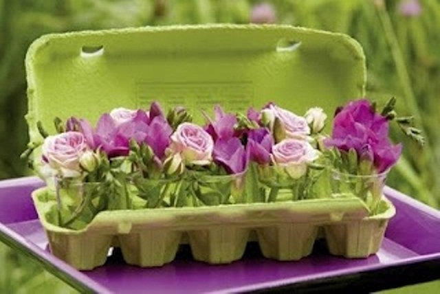 a green carton with purple and bloom arrangements is a cool Easter decoration