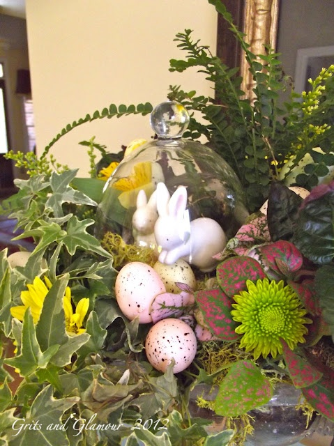 a lush spring centerpiece with lots of greenery, blooms and fake bunnies and pink eggs
