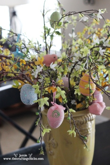 blooming branches with colorful fake eggs and birdies for Easter
