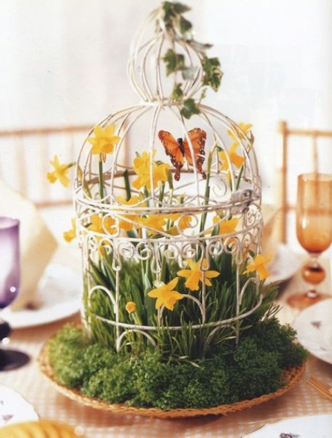 a fake bird cage with grass inside and fake yellow blooms and greenery for Easter