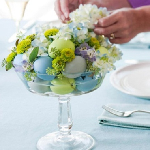 a glass bowl with pastel eggs and pastel spring blooms is a chic Easter centerpiece