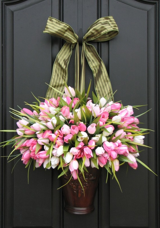 a lush pink and white tulip arrangement in a metal vase with a green bow for Easter front decor