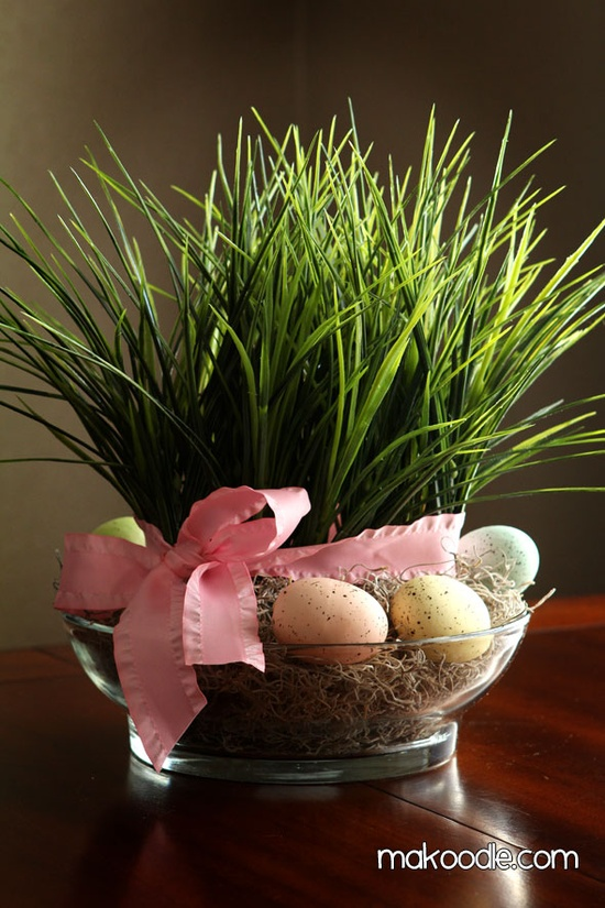 a glass bowl with hay, grass and eggs plus a pink ribbon is a fresh Easter decoration