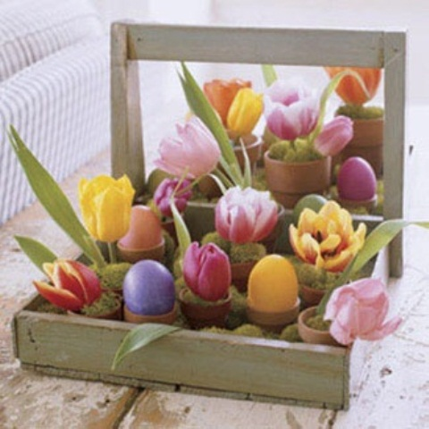 a crate with moss and colorful blooms, eggs and greenery in pots for Easter decor
