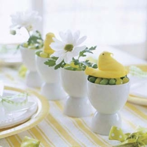 white egg cups with candies, fake chicks and spring blooms for Easter decor